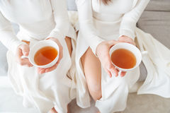 Two women in white dresses holding cups of tea Royalty Free Stock Photos