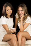 Two women white dresses sit phone one smile Stock Photography