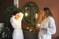 Two women in white robes drinking tea after spa treatments royalty free stock image