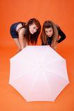 Two Women And A White Umbrella. Two young women bending over while holding a white umbrella in front of them, obscuring their legs from approximately the knees royalty free stock photography