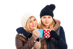 Two women in winter clothes holding mug Royalty Free Stock Photos