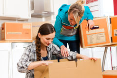 Two Women With Moving Box In Her House Stock Photos