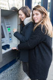 Two women withdraw money. Two standing in front of an ATM Stock Photography