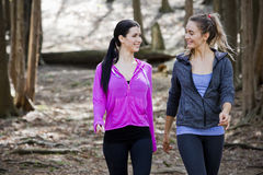 Two women wlaking in the middle of the woods Stock Image