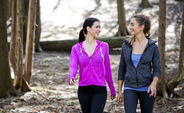 Two women wlaking in the middle of the woods Stock Photo