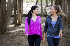 Two women wlaking in the middle of the woods Royalty Free Stock Photography