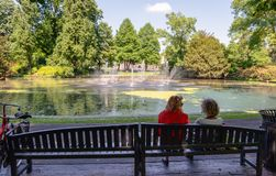 Two women on a wooden bench in the park. On sunny day in the spring season. In front of them is a large pond with duckweed and spraying fountains Stock Photo