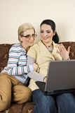 Two women work on laptop and converse Royalty Free Stock Photo