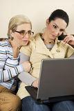 Two women work on laptop home Stock Images