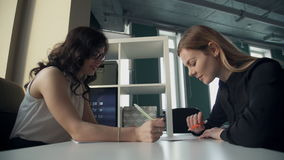 Two women work with some documents, write reports in office. Attractive woman with red full lips, dark curly long hair in white transparent top with gold chain stock video