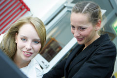 Two women working. Two young female students looking at notebook Royalty Free Stock Images