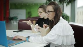 Two women working on a business project in a cafe and have lunch stock video