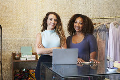 Two women working in clothing store looking to camera Stock Photography