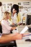 Two Women Working At Desks In Busy Creative Office Stock Images