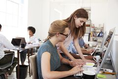 Two women working from a document in open plan office Stock Photos