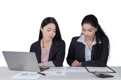 Two women working with documents on desk. Portrait of two asian businesswomen working on desk with financial chart and laptop Royalty Free Stock Photo