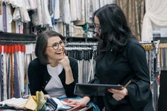 Two women working with interior fabrics digital tablet in showroom for curtains and upholstery fabrics, designer and buyer. Choosing fabrics in new interior stock photo