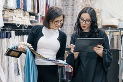 Two women working with interior fabrics digital tablet in showroom for curtains and upholstery fabrics, designer and buyer. Choosing fabrics in new interior royalty free stock photos