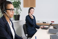 Two women are working in the office. A young business women with headset is sitting in front of a notebook. Another women with headset is sitting in the Royalty Free Stock Image
