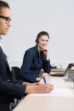 Two women are working in the office. A young business women with headset is sitting in front of a notebook. Another women is sitting in the foreground (blurred) Stock Photography