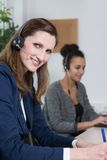 Two women are working in the office. A young business women with headset is writing at a document. Another women with headset is sitting in the background ( Stock Photography
