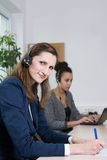 Two women are working in the office. A young business women with headset is writing at a document. Another women with headset is sitting in the background ( Stock Image