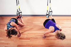 Two women working out with straps. Two young women are doing bodyweight exercises with straps Stock Photo