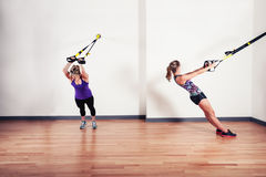 Two women working out with straps Royalty Free Stock Images