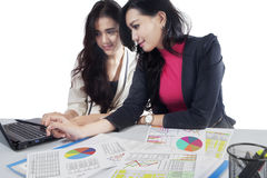 Two women working with paperwork and laptop Stock Image