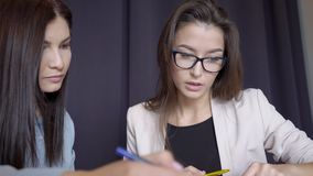 Two women are working at table in modern office. stock footage