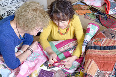 Two women working on their quilting. Two women working on their patchwork in the workshop Stock Photography