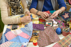 Two women working on their quilting. Two women working on their patchwork in the workshop Stock Image