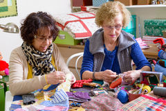 Two women working on their quilting. Two women working on their patchwork in the workshop Royalty Free Stock Photos