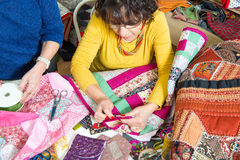 Two women working on their quilting. Two woman working on their patchwork in the workshop Stock Photos