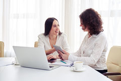 Two women working together with gadgets in the office Royalty Free Stock Photography