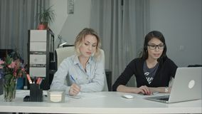 Two women working together in the office. Brunette in headseat dictating data from the laptop, while blonde girl making notes. Professional shot on BMCC RAW Stock Images