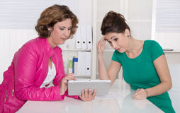 Two women working together at office with tablet-pc. Teamwork at office with tablet-pc Royalty Free Stock Photo