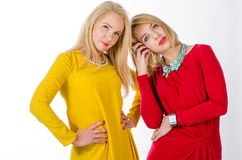 Two women in yellow and red dresses Stock Photos