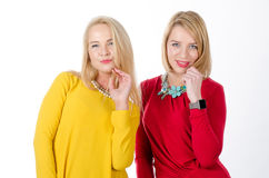 Two women in yellow and red dresses Stock Photo