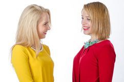 Two women in yellow and red dresses smiling at each other Stock Photos