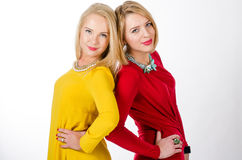 Two women in yellow and red dresses Royalty Free Stock Photography