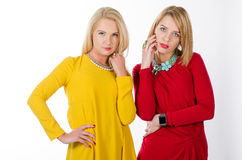 Two women in yellow and red dresses Stock Image