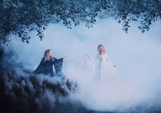 Two women yin yang in the fog. The Dark Magician meets a bright sorceress. Powerful witches conjure in the forest. Black royalty free stock image