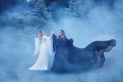 Two women yin yang in the fog. The Dark Magician meets the Light Elf a sorceress. Mighty witches are dancing in the Stock Photos