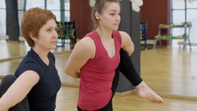 Two women is in yoga training in sports club. Flexible females stretch bodies while standing in modern studio indoors. Brunettes practice concentratedly stock video footage