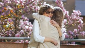 Two women, young and mature, hugging on a sunny spring morning against the background of a blossoming magnolia tree stock video footage