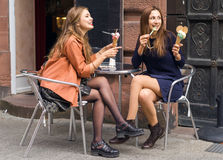 Two womens eating ice cream. Two women eating ice cream in town Royalty Free Stock Image