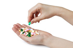 Two womens hands hold color pharmaceutical pills Royalty Free Stock Photos