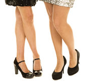 Two womens legs facing black heels. Two women's legs standing together, in their black heels and dresses Stock Image