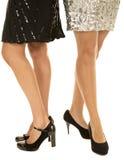 Two womens legs shiny dresses Stock Photos